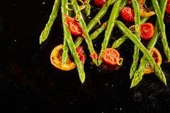 Espárrago salteado sabroso con los tomates de la carne asada Fotos de archivo libres de regalías