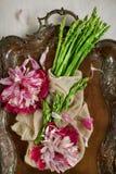 Espárrago verde fresco adornado en una placa de metal del vintage en la placa de madera blanca de la cocina con las peonías hermo Imágenes de archivo libres de regalías