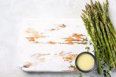 Espárrago verde fresco y viejo tablero de madera blanco Imagen de archivo