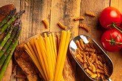 Espárrago, y la alcachofa y la puntilla de tomates y del espagueti rojo dulce del pimienta e italiano en una tabla de cortar con  imagen de archivo
