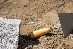Espátula com um punho de madeira na areia com uma parte de granito fotografia de stock