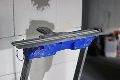 Espátula contra a parede do concreto ventilado reparo no apartamento ou na casa, materiais de construção, obras imagem de stock