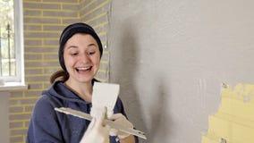 Espátula sonriente feliz de la tenencia de la muchacha y reparaciones el hacer en su apartamento almacen de video
