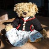 Esp?cimen ?nico, peque?a muchacha que hace punto - oso de peluche, Baviera del fom de la muchacha que lleva la ropa tradicional fotos de archivo