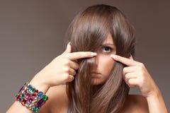 Espía tímido de la muchacha a través del pelo Imagen de archivo
