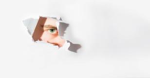 Espíe el ojo humano que mira a través de un agujero en un papel, en la búsqueda Imágenes de archivo libres de regalías