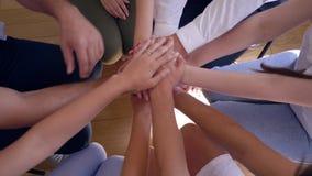 Espíritu de equipo, gente joven que hace la pila de las manos que se mueven arriba y abajo de sentarse en círculo en terapia del  almacen de video