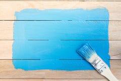 Espaço azul da pintura com o pincel no fundo de madeira imagem de stock