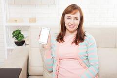 Espaço branco vazio na tela do smartphone Mulheres de negócios que lêem o newspaer e que prendem o móbil Mulher atrativa de sorri Foto de Stock