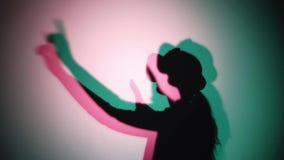 Espaço colorido abstrato com sombra da mulher em auriculares de VR vídeos de arquivo