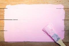 Espaço cor-de-rosa da pintura com o pincel no fundo de madeira imagens de stock
