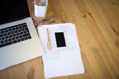 Espaço de funcionamento com laptop aberto, telefone celular moderno e originais de papel Fotos de Stock Royalty Free