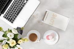 Espaço de trabalho colocado liso feminino com portátil, copo do chá, macarons, carta de amor e flores na tabela branca Zombaria d imagens de stock royalty free