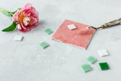 Espaço de trabalho com faca de paleta, pintura da lona, flor da tulipa e mosaico no backround cinzento fotografia de stock