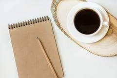 Espaço de trabalho com o caderno do papel do ofício, lápis, xícara de café no fundo branco copie o espaço para seu texto Fotografia de Stock
