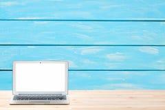 Espaço de trabalho conceptual ou conceito do negócio Laptop com a tela branca vazia na tabela de madeira clara contra a parede de Imagens de Stock