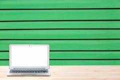 Espaço de trabalho conceptual ou conceito do negócio Laptop com a tela branca vazia na tabela de madeira clara contra a parede de Foto de Stock