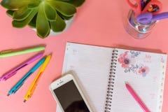 Espaço de trabalho da casa da vista superior com o calendário aberto no fundo cor-de-rosa imagem de stock royalty free
