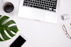 Espaço de trabalho da mesa de escritório domiciliário com copo de café, vidros, smartphone fotografia de stock royalty free
