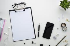 Espaço de trabalho da mesa de escritório domiciliário com os acessórios do smartphone e do escritório no fundo branco Fotografia de Stock