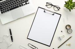 Espaço de trabalho da mesa de escritório domiciliário com os acessórios de prata do caderno e do escritório no fundo branco Fotografia de Stock