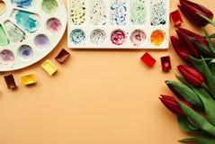 Espaço de trabalho do artista com as tulipas do ramalhete, as cubetas da aquarela e as paletas vermelhas em um fundo pálido da co Foto de Stock