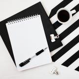 Espaço de trabalho de Minimalistic com livro, caderno, lápis, xícara de café em fundo preto e branco listrado Opinião superior do imagens de stock