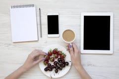 Espaço de trabalho moderno com mãos, o caderno, o lápis, o smartphone, a tabuleta, as bagas e o copo de café fêmeas no fundo de m fotografia de stock royalty free