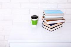 Espaço de trabalho perto da parede de tijolo Xícara de café e muitos livros Copie o espaço e o foco seletivo Foto de Stock