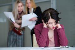 Espaço de trabalho ruidoso cansado da mulher do zumbido do escritório imagem de stock