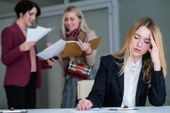 Espaço de trabalho ruidoso da dor de cabeça da mulher do zumbido do escritório fotografia de stock royalty free