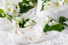 Espaço feminino à moda com as flores brancas da árvore de maçã no vaso Ainda vida minimalistic denominada Foto de Stock