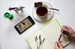 Espa?o de trabalho com bloco de notas, copo do ch? em um fundo branco Configura??o lisa, mesa de escrita da mesa de escrit?rio da foto de stock