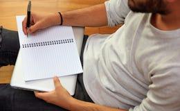 Espace de travail à la maison Écriture d'étudiant, séance sur le plancher Photographie stock libre de droits