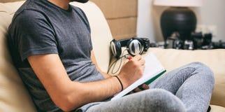 Espace de travail à la maison Écriture d'étudiant, séance sur un sofa Image stock