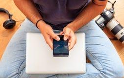 Espace de travail à la maison Équipez tenir un smartphone, se reposant sur le plancher Images stock