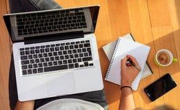 Espace de travail à la maison Étudiant travaillant avec un ordinateur portable sur le plancher Images stock