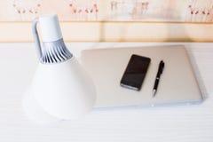 Espace de travail à la maison avec la lampe de table, le macbook, le téléphone et le stylo Photos stock
