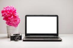 Espace de travail élégant avec l'ordinateur portable, fournitures de bureau, appareil-photo, Photos stock