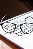 Espace de travail avec des lunettes sur l'ordinateur portable Photo stock