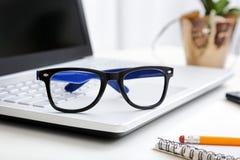 Espace de travail avec des verres de hippie sur l'ordinateur portable Photo stock