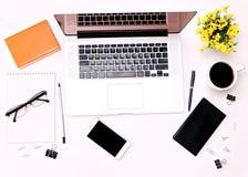 Espace de travail avec des verres et des fleurs de café de téléphone portable de clavier d'ordinateur portable Images stock