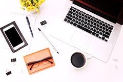 Espace de travail avec des verres et des fleurs de téléphone portable de clavier de café d'ordinateur portable Image stock