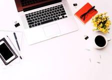Espace de travail avec des verres et des fleurs de téléphone portable de clavier d'ordinateur portable de café Image stock