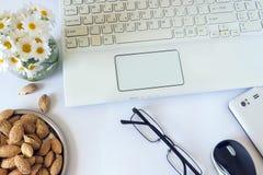 Espace de travail avec l'ordinateur à la maison, un bureau avec des fleurs et le blanc Photos stock