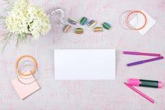 Espace de travail avec l'ordinateur, hortensias de bouquet, presse-papiers Accessoires de mode du ` s de femmes sur le fond rose  Photo stock