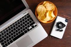 Espace de travail avec l'ordinateur portable, l'éclair-joueur et la cuvette de puces sur la table en bois Concept de mauvaises ha Images libres de droits