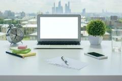 Espace de travail avec l'ordinateur portable blanc Photographie stock libre de droits