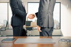 Espace de travail avec l'ordinateur portable et hommes d'affaires se serrant la main en o moderne Image libre de droits