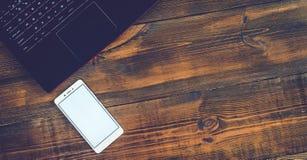Espace de travail avec l'ordinateur portable et le smartphone sur le bureau en bois dur Photo libre de droits